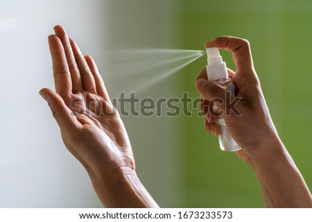 Caucasian woman wipes her hands with an alcohol-based hand-washing spray as a preventive hygiene measure against coronavirus ( Sars-CoV-2, Covid-19) infection. Antibacterial hand sanitizer gel.