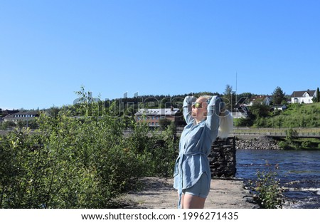 Caucasian Woman with blond hair, sunglasses jeans shirt and shorts standing on rocks relaxing and enjoying herself during summer vacation in front of Glomma river in Kongsvinger, Norway