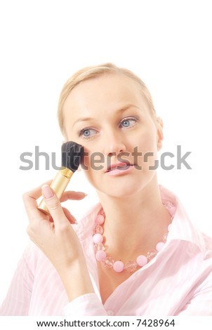 Caucasian woman with makeup brush applying face powder