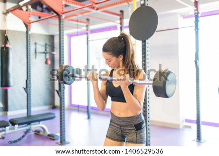 Caucasian woman with muscular physique lifting barbell during training at health club