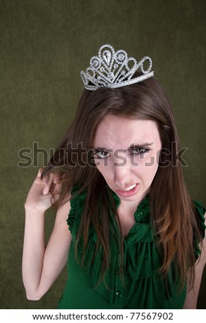 Caucasian woman with tiara plays with her hair