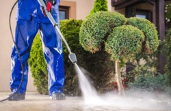 Caucasian Worker in His 30s with Pressure Washer Cleaning Residential Driveway. Garden and Home Surrounding Maintenance.