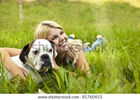 Caucasian young adult blond woman outdoor with boxer dog fall time