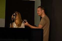 Caucasian young attractive musical singers in recording studio rehearsal vocal performance with microphone.