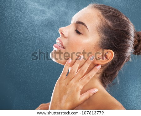 caucasian young beautiful woman with water sparks on blue background