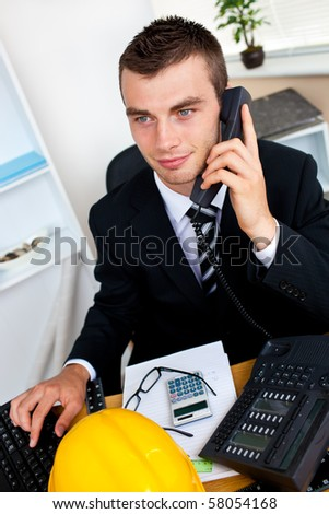 Caucasian young businessman talking on phone sitting at his desk in his office