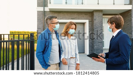 Caucasian young happy couple in medical masks buying house at outskirt and talking with male real-estate agent holding tablet device in hands. Outdoor. Coronavirus pandemic concept.