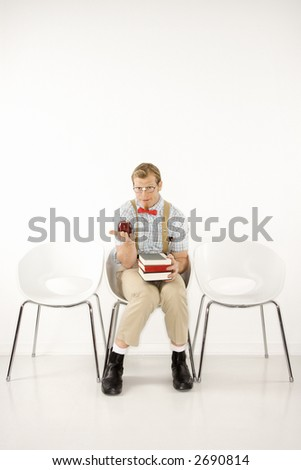 Caucasian young man dressed like nerd looking at viewer sitting with books and holding out apple.