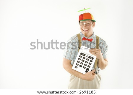 Caucasian young man dressed like nerd wearing beanie and smiling while holding large calculator.