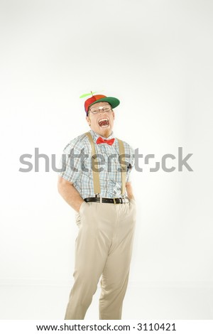 Caucasian young man dressed like nerd wearing propeller cap with hands in pockets looking at viewer with mouth open.