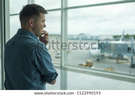 Caucasian young man is afraid to flight standing in terminal near window. Aerophobia concept Сток-фото ©