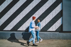 Caucasian young man with coffee to go met african american hipster girl during walk in modern city with creative graffiti on wall.Multicultural friends in denim casual wear strolling on street