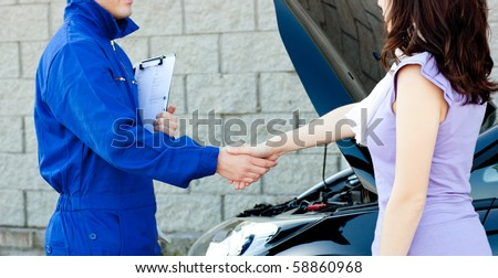 Caucasian young mechanic shaking hands with a female customer in front of a car