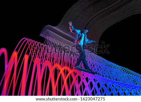 Caucasian young skateboarder riding on dark neon lighted line background. Training in action and motion on colorful waves. Concept of hobby, healthy lifestyle, youth, action, movement, modern style. Foto d'archivio ©