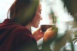 Caucasian young woman enjoying coffee drinking in cafe, close up