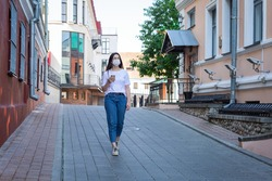 Caucasian young woman in protective mask on her face walks alone along the street, listens to music. Concept: solo walks great outdoors in uninhabited places. Europe. City environment. Summer morning.