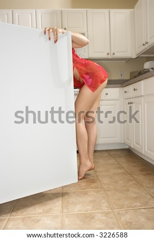 Caucasian young woman in sexy red lingerie looking in refrigerator. - stock photo