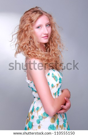 caucasian young woman with light long curly hair over gray background