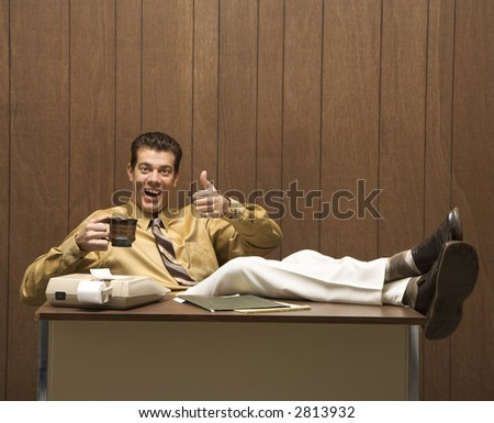 Caucasion mid-adult retro businessman sitting with feet propped on desk drinking coffee giving a thumbs up.