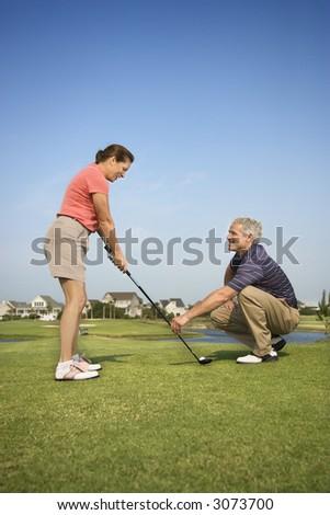 Caucasion mid-adult woman holding golf club while mid-adult man kneels holding club teaching.