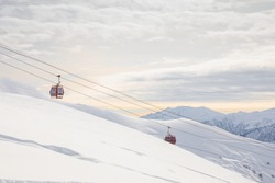 Caucasus Mountains at morning. Gudauri ski resort, Georgia. Gondolas, cable cars and Ski slope and chair-lift are moving above the fresh snow with mountains and clouds in the background.
