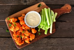 Cauliflower buffalo wings with celery and ranch dip. Top view on a wood paddle board. Healthy eating, plant based meat substitute concept.