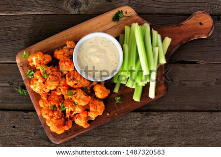 Cauliflower buffalo wings with celery and ranch dip. Top view on a wood paddle board. Healthy eating, plant based meat substitute concept. Foto stock ©