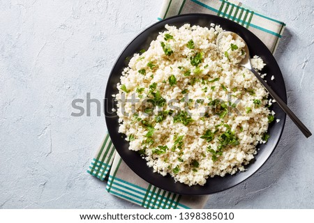 Cauliflower rice or couscous mixed with finely chopped parsley in a black bowl on a white concrete table, healthy eating, low calories food, horizontal view from above, flatlay, empty space Foto stock ©