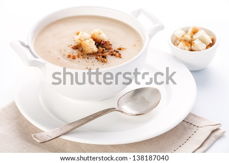Cauliflower soup with croutons on white background