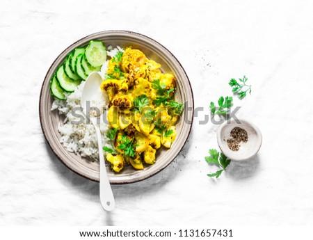 Cauliflower, squash, zucchini, turmeric, yogurt stir fry with rice on a light background, top view. Vegetarian diet healthy food concept