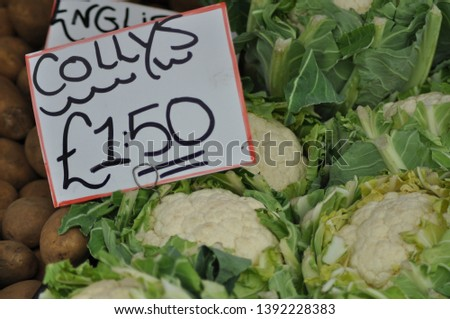 Cauliflowers for sale at a farmers market pictured in front of a sign reading Collys £1.50.