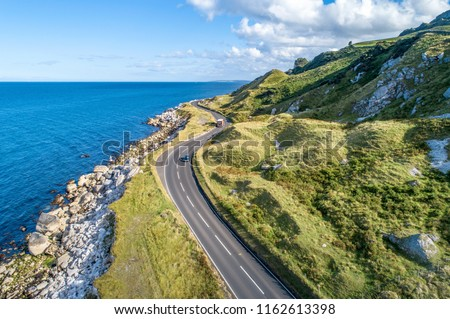 Photo of  Causeway Coastal Route with cars, a.k.a. Antrim Coastal Road on eastern coast of Northern Ireland, UK.