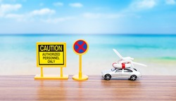 Caution and no entry sign with model car and beach chair and life buoy over blurred beach background, summer season, holiday and vacation trip