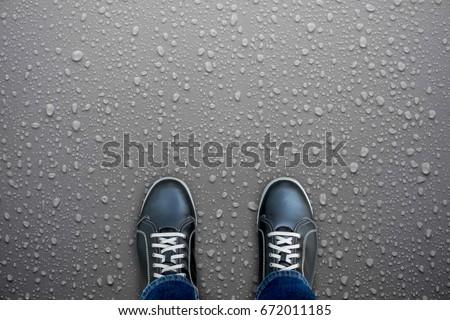 Caution, wet floor. Black shoes standing on wet floor. Slippery and dangerous. Need careful walk. #672011185