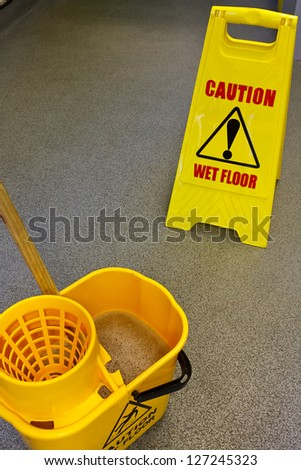 Caution wet floor health and safety sign with mop and bucket Stock foto ©