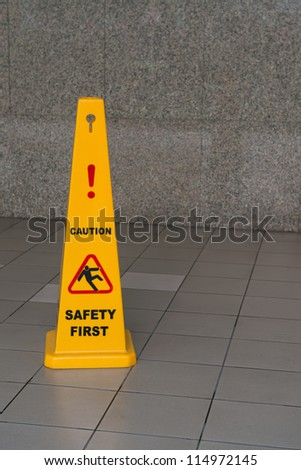 Caution wet floor sign on tiled floor with stone wall on background