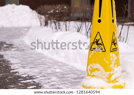 Caution Wet Floor. Slippery Yellow Surface Sign On Red Brick Building And Snow Heap. Slippery Slope. Icing Concept: Be Aware Of Slippery Road And Watch Your Step, Please.