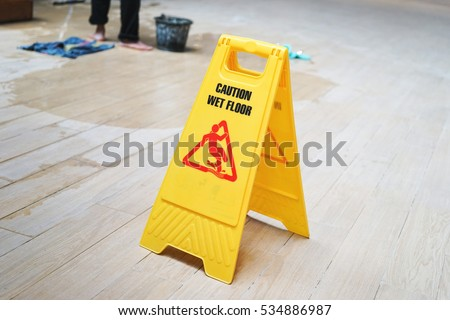 caution wet floor warning sign with blurred worker mopping floor #534886987