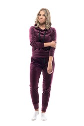 Cautious young woman in leisure casual clothes looking at camera carefully. Full body isolated on white background.
