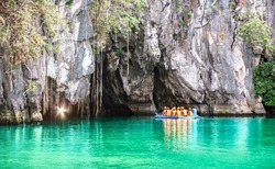 Cave entrance of Puerto Princesa subterranean underground river with longtail boat - Wanderlust travel concept at Palawan exclusive Philippine destination - Vivid filter with bulb torch light sunflare