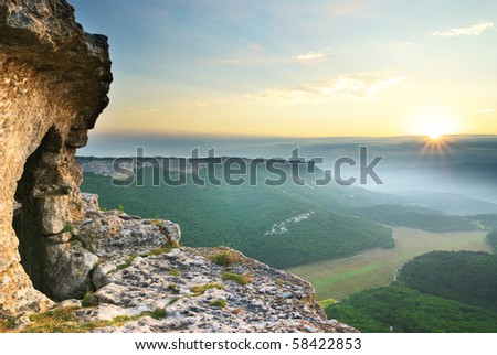 Cave in mountain on sunrise. Nature composition.