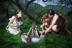 Cave people dressed in animal skin making fire in the forest