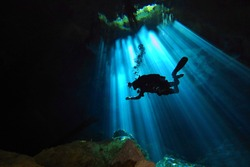 Cave technical diver swimming from the light into darkness. Scuba diver in the cenote and sun rays. Underwater photography from the cave exploration.