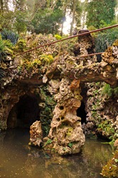 Cave, underground galleries and stepping stones over pond at Quinta da Regaleira, Sintra, Portugal