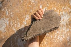 Caveman's hand holding sharp rock. Hand of stone age man holding sharp stone.