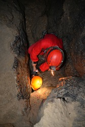 Caver in overalls in a narrow cave. Rescue from a narrow place of a stone cave. Historic mining light. Cave rescue. Spelunking, extreme sport. Caver performs out of a cave.