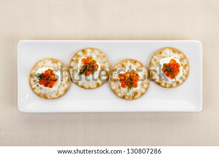 Caviar appetizer with goat cheese and crackers on white plate from above