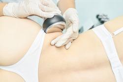 Cavitation rf body treatment. Female ultra sound lipo machine. Spa contouring. Doctor hands.