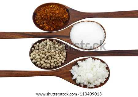Cayenne pepper, salt, pepper and sugar in a wooden spoon. Isolated on white.