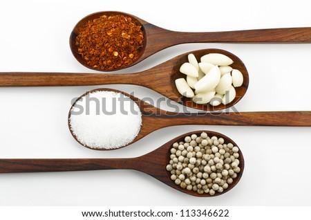 Cayenne pepper, sugar, garlic and pepper,Arranged in a wooden spoon.